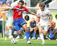 Leonardo Gonzalez (12) of Costa Rica sails past Miroslav Szymkowiak (10) of Poland. Poland defeated Costa Rica 2-1 in their FIFA World Cup Group A match at FIFA World Cup Stadium, Hanover, Germany, June 20, 2006.