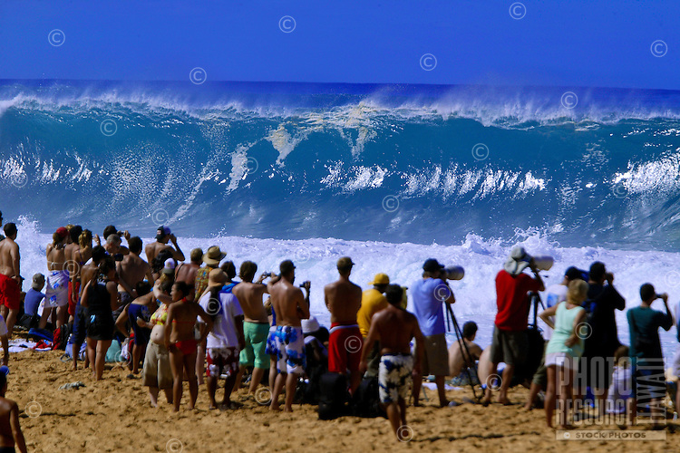 people gather to watch the excitement of big wave surfing at Pipeline