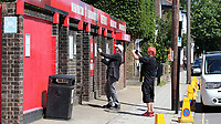 A couple of Brentford supporters take photos of the outside of Griffin Park ahead of their last ever match during Brentford vs Swansea City, Sky Bet EFL Championship Play-Off Semi-Final 2nd Leg Football at Griffin Park on 29th July 2020