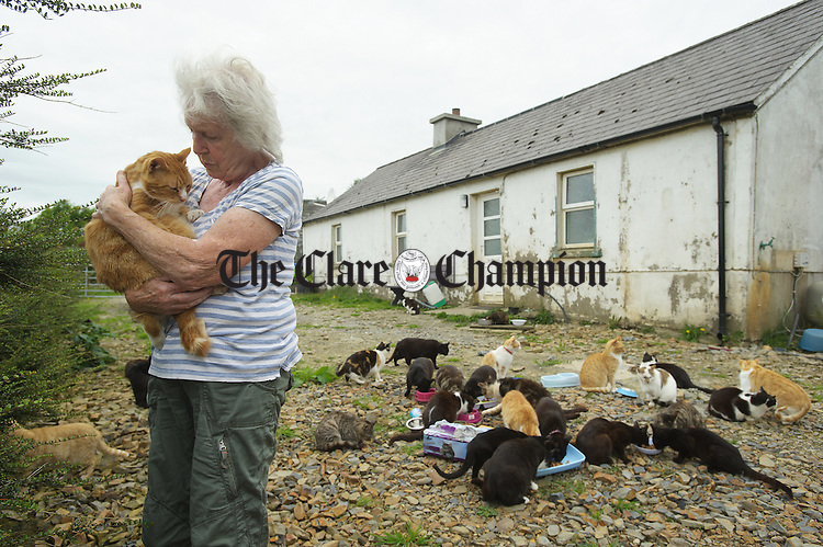 """Dr. Rhona M. Lucas cuddles one of her favorites while feeding some of her hundred and fifty cats at the """"An Cat Dubh Sanctuary"""" in Clounlaheen, near the Hand. Photograph by John Kelly."""