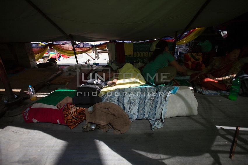A homeless boy sleeps in a tent near the destroyed Shoyembho temple, just outside Kathmandu, Nepal