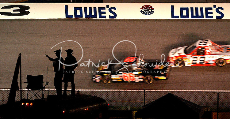 Race fans are silhouetted against the Lowe?s Motor Speedway track as they cheer on drivers during the NASCAR Hardee?s 200 truck race. This was the first truck race ever run at Lowe?s Motor Speedway.