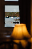 View through a cottage window of New Grimsby Harbour, Tresco, Isles of Scilly, Cornwall, UK with the island of Bryher in the distance.  21/09/09