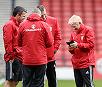 Gordon Strachan sharing something funny on his phone with his backroom staff