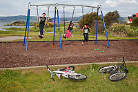 Maori Children Playing on Swings, Ohinemutu Maori Village, Rotorua, north island, New Zealand.