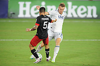 WASHINGTON, DC - AUGUST 25: Adam Buska #9 of New England Revolution battles for the ball with Junior Moreno #5 of D.C. United during a game between New England Revolution and D.C. United at Audi Field on August 25, 2020 in Washington, DC.