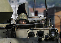 A marine looks out over an armoured vehicle during an operation at Complexo da Penha, Rio de Janeiro, Brazil, November 25, 2010. Authorities in Rio de Janeiro try to control a fourth day of violence apparently orchestrated by drug gang members who have attacked police stations and burned cars in Rio de Janeiro city as protest by traffickers after being forced from their turf by police occupations of more than a dozen slums in the past two years..(Austral Foto/Renzo Gostoli)