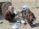 Iraq 2015 <br /> In the camp of Berseve, women and a little girl preparing bred <br /> Irak 2015 <br /> Au camp de Berseve, femmes et une petite fille preparant du pain.