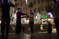 """Rome, Italy. 12th October, 2021. This evening, the marvelous scenario of Piazza Navona (1.) in Rome was the stage for a Silent Disco gathering. People armed of wireless headphones congregated and danced in silence in front of the Fontana del Moro (Moor Fountain).<br /> «A silent disco or silent rave is an event where people dance to music listened to on wireless headphones. Rather than using a speaker system, music is broadcast via a radio transmitter with the signal being picked up by wireless headphone receivers worn by the participants. Those without the headphones hear no music, giving the effect of a room full of people dancing to nothing. In the earliest days of silent discos, before 2005, there would be only one channel available to listen to music through. Over time, the technology moved along to where there were two, and later technology allowed for a third channel that three separate DJs could broadcast over at the same time. Silent discos are popular at music festivals as they allow dancing to continue past noise curfews. Similar events are """"mobile clubbing"""" gatherings, where a group of people dance to the music on their personal music players […]» (2.).<br /> <br /> Footnotes and Links:<br /> 1. (Source, Wikipedia.org) https://en.wikipedia.org/wiki/Piazza_Navona <br /> 2. (Source, Wikipedia.org) https://en.wikipedia.org/wiki/Silent_disco"""
