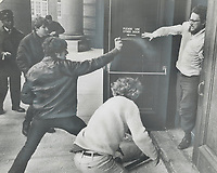 Battling on campus of University of Toronto outside a rally where Quebec union leader Michel Chartrand and Montreal lawyer Robert Lemieux were speaking; a youth claiming to be a member of rightwing Edmund Burke Society aims a spray into the face of student<br /> <br /> 1971<br /> <br /> PHOTO :  Bob Olsen - Toronto Star Archives - AQP