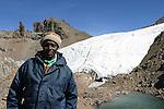 Guide John Maina à Austrian Hutt devant le glacier de Lewis. Il y a dix ans, la langue glaciaire recouvrait le lac au premier plan Mont Kenya