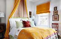 The headboard in the master bedroom has been upholstered in a striped deckchair canvas, complimented by a deep yellow bed hanging, blind and bed cover