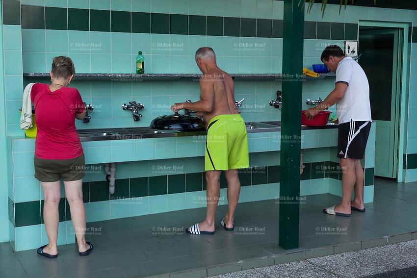 Switzerland. Canton Ticino. Tenero. Camping Campofelice. A woman and two men wash kitchen plates in public facilities. 21.07.2018 © 2018 Didier Ruef