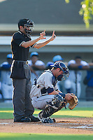 Home plate umpire Reid Joyner signals the count as Princeton Rays catcher Nick Ciuffo (14) gets ready to call the next pitch during the game against the Burlington Royals at Burlington Athletic Park on July 11, 2014 in Burlington, North Carolina.  The Rays defeated the Royals 5-3.  (Brian Westerholt/Four Seam Images)