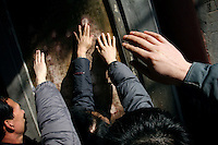 CHINA. Worshippers trying to touch certain chinese charachters on a plaque during Chinese New Year in Baiyun Temple in Beijing.  Chinese New Year, or Spring Festival, is the most important festival and holiday in the Chinese calendar In mainland China, many people use this holiday to visit family and friends and also visit local temples to offer prayers to their ancestors. The roots of Chinese New Year lie in combined influences from Buddhism, Taoism, Confucianism, and folk religions.  2008.