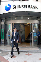 A man exits a branch of the Shinsei Bank in central Tokyo, Japan. Burdened by heavy subprime-related losses, Shinsei Bank has announced the sale of its Tokyo head offices to a real estate fund connected with Morgan Stanley..
