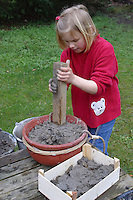 Kinder basteln Nisthilfen für Wildbienen und Wespen, Insektenhotel, Insekten-Hotel, feuchter Lehm wird in einem Gefäß gestampft, im Lehm können Wildbienen ihre Höhlen bauen und nisten