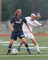 Seacoast United Phantoms player Carly Gould (3) attempts to control the ball as Boston Aztec defender Kerri Zerfoss (28) pressures. In a Women's Premier Soccer League (WPSL) match, Boston Aztec (white) defeated Seacoast United Phantoms (blue), 3-0, at North Reading High School Stadium on Arthur J. Kenney Athletic Field on on June 25, 2013.