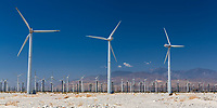 Windmill turbines farm in the desert under a blue sky, with Joshua Tree National Park mountains in the background, near Palm Springs California USA