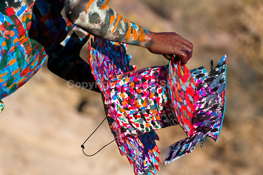 """A Cora Indian boy, with body painted colorfully, paints his multi-colored hat before the sacred ritual celebration of Semana Santa (Holy Week) in Jesús María, Nayarit, Mexico, 22 April 2011. The annual week-long Easter festivity (called """"La Judea""""), performed in the rugged mountain country of Sierra del Nayar, merges indigenous tradition (agricultural cycle and the regeneration of life worshipping) and animistic beliefs with the Christian dogma. Each year in the spring, the Cora villages are taken over by hundreds of wildly running men. Painted all over their semi-naked bodies, fighting ritual battles with wooden swords and dancing crazily, they perform demons (the evil) that metaphorically chase Jesus Christ, kill him, but finally fail due to his resurrection. La Judea, the Holy Week sacred spectacle, represents the most truthful expression of the Coras' culture, religiosity and identity."""