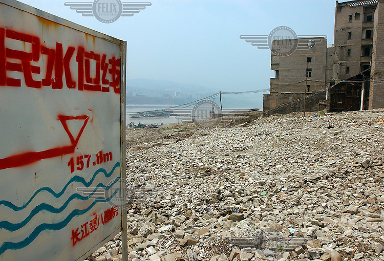 © Dermot Tatlow / Panos Pictures..04/2003. Old Fengdu, Sichuan province, China...Sign indicating the water level of the second phase of flooding of the Yangtze river. and the rubble of Old Fengdu