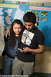 Education High School male and female students couple in corridor checking cell phone between classes