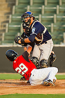 Catcher Anthony Aguilera #16 of the Asheville Tourists tags out Carlos Sanchez #29 of the Kannapolis Intimidators at home plate at Fieldcrest Cannon Stadium on July 28, 2011 in Kannapolis, North Carolina.  The Intimidators defeated the Tourists 2-1 in 10 innings.   (Brian Westerholt / Four Seam Images)