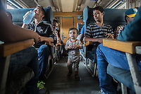 interno di un treno di migranti interior of a train of migrants  bambino e signore che beve acqua child and man drinking water