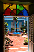 Courtyard and colorful stained glass in small hotel downtown in Cienfurgos Cuba