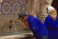 Fez, Morocco - Passersby Refresh Themselves at the Nejjarine Public Fountain in the Old City of Fez.