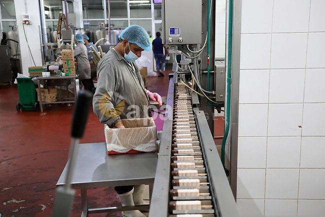 Palestinian workers work inside an ice cream factory in Gaza city, on August 8, 2021. The owners of ice-cream factories in the Gaza Strip suffer from a lack of production during the most demanding seasons during the summer, as a result of the difficult economic crises in the Gaza Strip, and power outages for continuous hours, which made this season come against expectations. Photo by Ashraf Amra