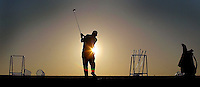As the sun sets over the LPGA International Golf Course practice range, Ralph Knoll, of New Smyrna Beach, seen through his spare golf clubs, takes full advantage of the sun and warmer weather to practice his swing Tuesday afternoon, January 14, 2003 in Daytona Beach.(Kelly Jordan)..**FOR SPORTS ELITE SERIES**