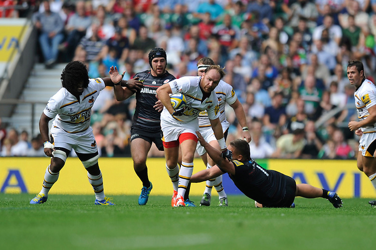 Andy Goode of Wasps breaks free from the tackle of Richard Barrington of Saracens during the Premiership Rugby Round 1 match between Saracens and Wasps at Twickenham Stadium on Saturday 6th September 2014 (Photo by Rob Munro)