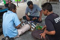 Yogyakarta, Java, Indonesia.  Men Playing Chess in the Prambanan Temple Compound.