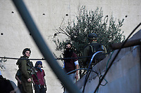 Israeli soldiers try to keep rioting Jewish settler youths from attacking a Palestinian house. Violence erupted as the Israeli army evicted a group of settlers from a disputed building in Hebron. The Israeli high court had rejected the settlers' claim that they legally bought the house from its Palestinian owner. As the house became a symbol of defiance, the few families living there were joined by a mob of some 1,500 radical right-wing youths, who went on a rampage and attacked Palestinians in the mixed West Bank city.