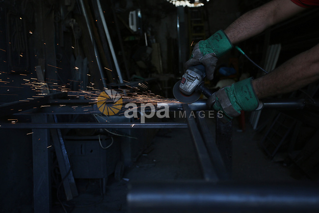Palestinian blacksmith, works at blacksmith workshop, marking International Workers' Day, in the West Bank city of Nablus, on May 01. 2021. Youth (19- 29 years) are the most group suffering from unemployment. Thus, the unemployment rate among youth reached about 39%; 24% in the West Bank and 67% in Gaza Strip. Moreover, the youth graduates of those who hold a scientific qualification of an intermediate diploma or higher are the most group suffering from unemployment, as this rate reached about 54%; (36% in the West Bank and 79% in Gaza Strip). Photo by Shadi Jarar'ah