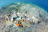 pollution, marine debris, plastic wastes, accumulated on a sandy underwater slope in Komodo National Park, Indonesia, Indo-Pacific Ocean