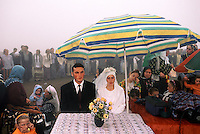 Duzcoy Wedding. Weddings occur at the peak of Yayla migration in the summer.  The couple waits for a ceremony to begin.<br /> Turkey's Black Sea coast has the highest peaks close to a sea anywhere in the world. The migration from summer fishing to highland shepherding has always been a part of the culture.  Mountain homes are called Yaylas (YIY-luz), and most families have more than one.  <br /> Families fish at the coast, but as the temperatures rise, they move to a succession of homes higher in the mountain range.  These homes are community property and were bequeathed during the Ottoman period.