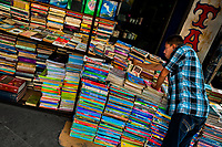 A Salvadoran bookseller arranges piles of used books stacked on the street in a secondhand bookshop in San Salvador, El Salvador, 11 April 2018. Large collections of worn-out books, mostly textbooks and educational paperbacks, are sold regularly in secondhand bookshops in the center of the city.
