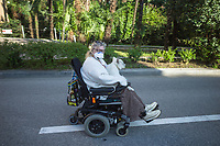 """Switzerland. Canton Ticino. Lugano. An elderly woman seated on a motorised wheelchair rides on the road with a dog on her knees. The aged woman wears a mask on the face to protect herself from the Coronavirus (also called Covid-19. Due to the spread of the coronavirus, the Federal Council has categorised the situation in the country as """"extraordinary"""". It has issued a recommendation to all citizens to stay at home, especially the sick and the elderly. The Federal Council (German: Bundesrat, French: Conseil fédéral, Italian: Consiglio federale, Romansh: Cussegl federal) is the seven-member executive council that constitutes the federal government of the Swiss Confederation. From March 16 the government ramped up its response to the widening pandemic, ordering the closure of bars, restaurants, sports facilities and cultural spaces. Only businesses providing essential goods to the population – such as grocery stores, bakeries and pharmacies – are to remain open. 19.03.2020 © 2020 Didier Ruef"""