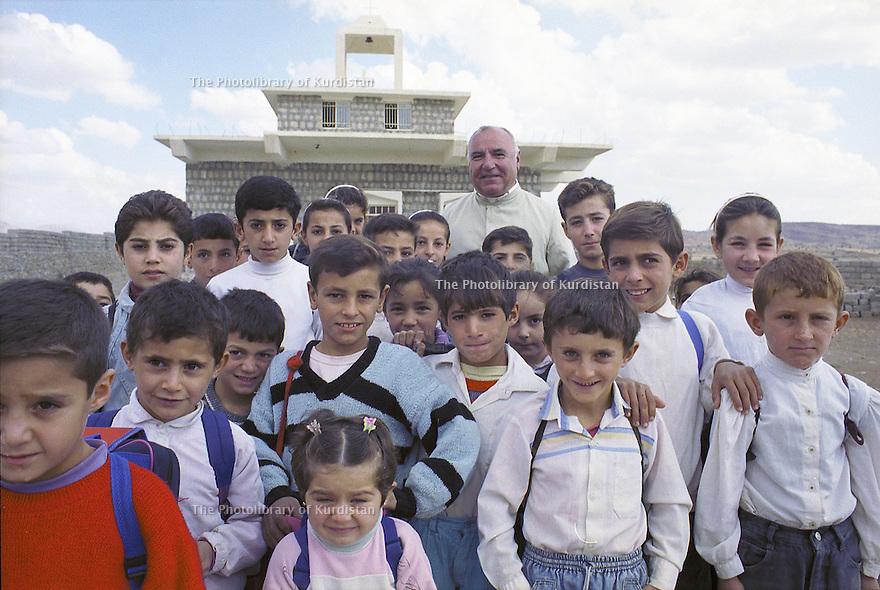 Iraq 2000<br /> Father Petros Harbol, Chaldean priest, with children in front the church of Levo<br /> Irak 2000<br /> Le père Pétros Harbol,prêtre chaldéen,  entouré des enfants du village devant l'église de Lévo