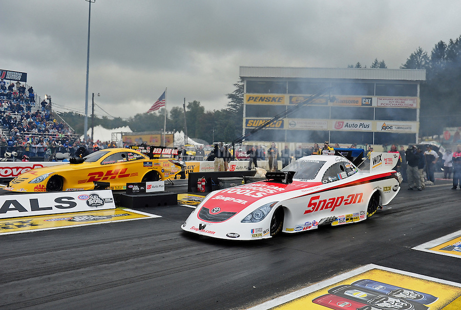 Oct. 2, 2011; Mohnton, PA, USA: NHRA funny car driver Cruz Pedregon (near lane) races alongside Jeff Arend during the Auto Plus Nationals at Maple Grove Raceway. Mandatory Credit: Mark J. Rebilas-