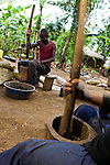 Man and woman mashing up vegetable peels and paper to create bricks to be used for fires instead of illegaly cut wood from protected area, Kibale National Park, western Uganda