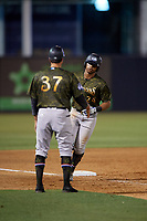 Tampa Tarpons third base coach Kevin Mahoney (37) congratulates Isiah Gilliam (24) as he rounds the bases after hitting a home run during a Florida State League game against the Daytona Tortugas on May 18, 2019 at George M. Steinbrenner Field in Tampa, Florida.  Daytona defeated Tampa 7-6.  (Mike Janes/Four Seam Images)