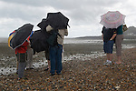Group of tourists on the beach at Whitstable Kent, summer rain  UK 2007 2000s