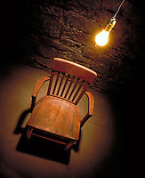 An interrogation room with wooden chair in cell with single, glaring lightbulb hanging directly overhead.