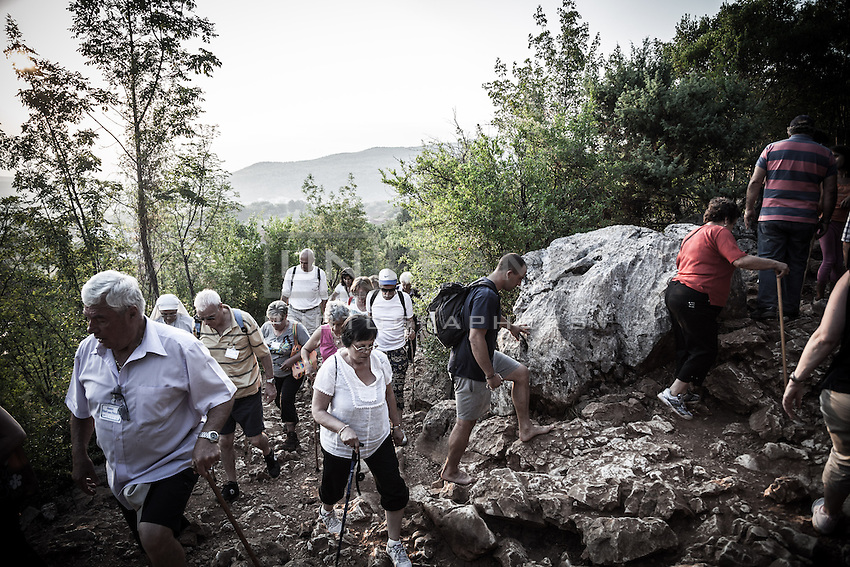 Pilgrims climb the Mt. Krizevac between the 15 stations of the  Via Crucis. Some of them walks barefoot. It takes 3 hours to climb through the steep and bumpy path.  The temperature hits 41°C. <br /> Medjugorje, Bosnia and Herzegovina. July 2012