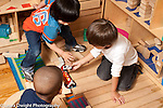 Education Preschool Headstart 3-4 year olds group of three boys playing with blocks and toy cars