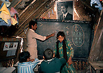 Marsh Arabs. Southern Iraq.  Marsh Arab children in school building. Traditional reed constructed building. Portrait of Saddam Hussein hanging from wall. 1984