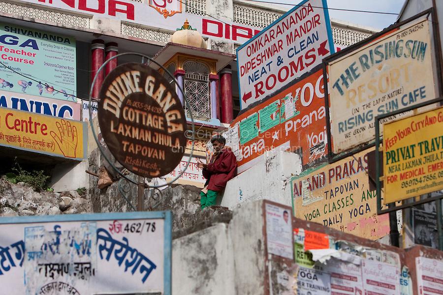 India, Rishikesh.  Advertisements near the footbridge over the Ganges (Ganga).  Restaurants, Yoga, Lodging.